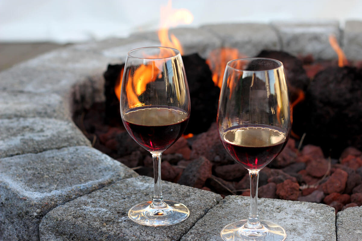 Picture of two wine glasses placed on stones in front of a fire pit