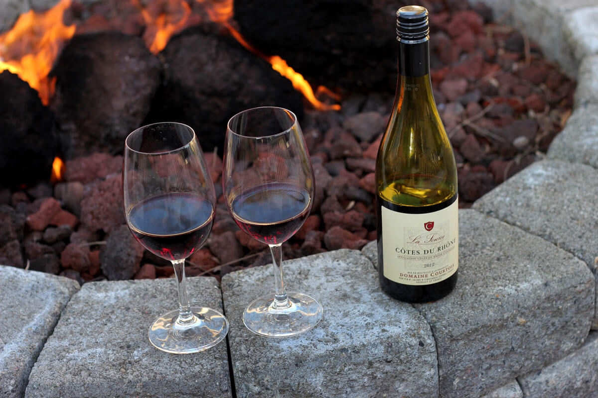 Picture of a wine bottle and two wine glasses sitting by an outdoor fire pit at Latte Da in Vancouver WA
